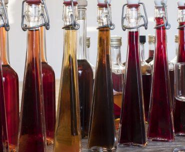 Das Bild zeigt bunte Likörflaschen.
