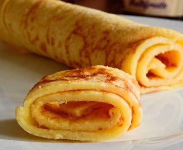 Das Bild zeigt aufgerollte Pfannkuchen, ein Streifen ist vorn abgeschnitten.