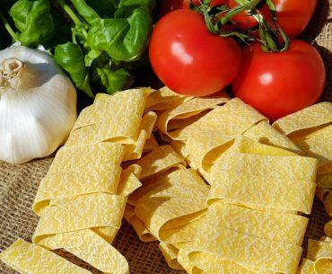 Das Bild zeigt ungekochte Tagliatelle, Tomaten, Knoblauch und Basilikum.