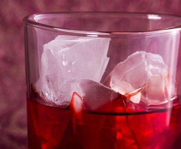 Das Bild zeigt ein Cocktailglas mit Eis und Getränk.