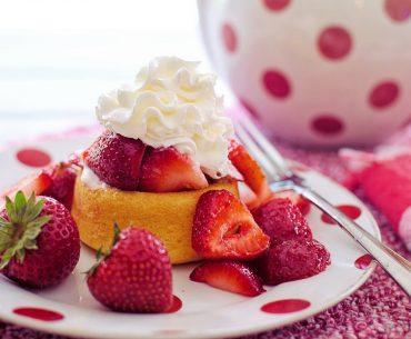 Das Bild zeigt einen kleinen Kuchen mit Erdbeeren und Sahne.